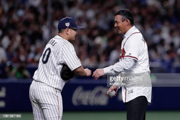 Former baseball player Kenshin Kawakami talks with catcher Tomoya Mori of Japan after throwing a ceremonial first pitch prior to the game five...