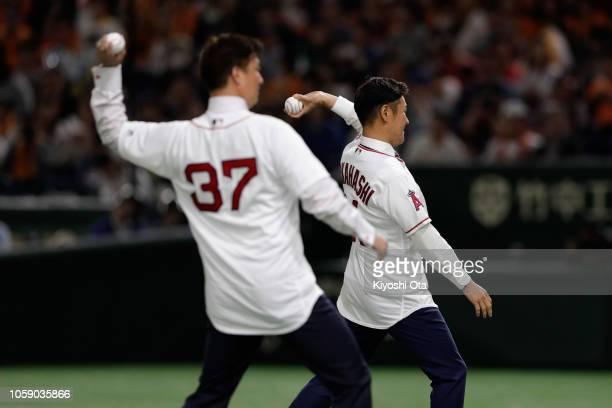 Former baseball players Hideki Okajima and Hisanori Takahashi throw ceremonial first pitch prior to the exhibition game between Yomiuri Giants and...