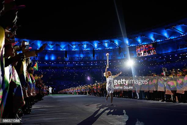 Former basketball player Hortencia Marcari carries the Olympic flame during the Opening Ceremony of the Rio 2016 Olympic Games at Maracana Stadium on...