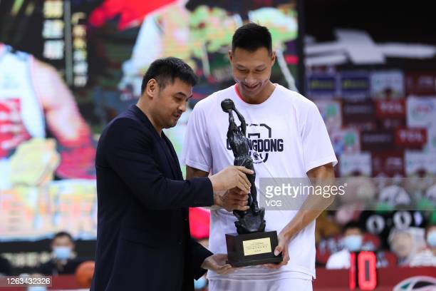 Former basketball player Liu Yudong hands over a trophy to Yi Jianlian of Guangdong Southern Tigers ahead of 2019/2020 Chinese Basketball Association...