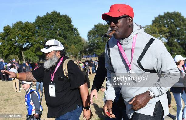US former basketball player Michael Jordan walks as he follows US golfer Tiger Woods' foursomes match on the second day of the 42nd Ryder Cup at Le...