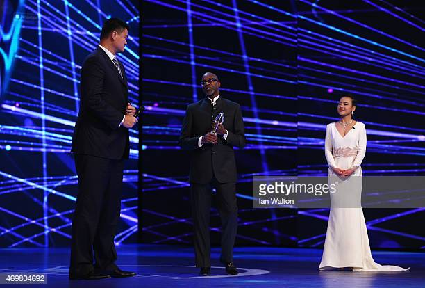 Former Basketball player Yao Ming of China is presented with the Laureus Spirit of Sport award by Laureus Chairman Edwin Moses as presenter Chen Chen...