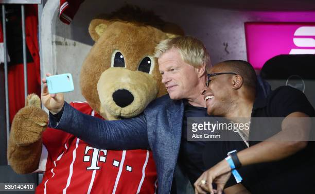 Former Bayern Muenchen players Oliver Kahn and Paulo Sergio take a selfie with mascot Berni on their mobile during the Bundesliga match between FC...