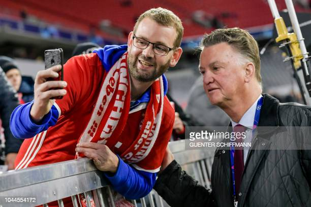 Former Bayern Munich coach Louis van Gaal poses with a fan for a photo prior to the UEFA Champions League Group E football match between Bayern...