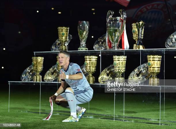 Former Bayern Munich's midfielder Bastian Schweinsteiger poses in front his won trophy's prior the farewell match for Bastian Schweinsteiger between...
