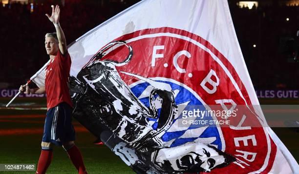 Former Bayern Munich's midfielder Bastian Schweinsteiger waves a flag of Bayern Munich, a gift of supporters, after his farewell match between his...