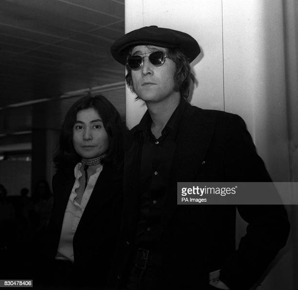 Former Beatle John Lennon in sunglasses and flat cap after he arrived at London Heathrow from New York With him came his wife Yoko Ono whose...