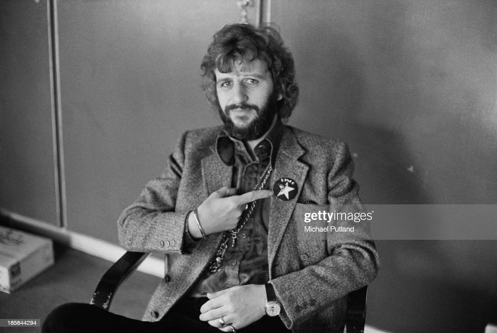 Former Beatles drummer Ringo Starr pointing to a badge with his name and a star motif, 22nd October 1973.