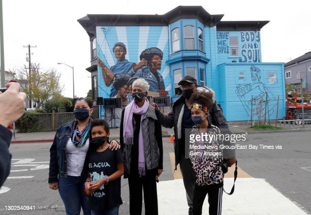 Former Black Panther Party member Ericka Huggins, center, poses for photos with others, while attending the unveiling of the mural by Rachel...