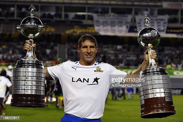 Former Boca Juniors footballer Martin Palermo holds Boca Juniors' two Copa Libertadores trophies before the start of his farewell football match at...
