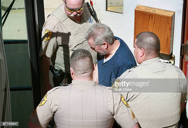 Former Bolingbrook Illinois police officer Drew Peterson is escorted by correctional officiers from the Will County Courthouse after his arraignment...