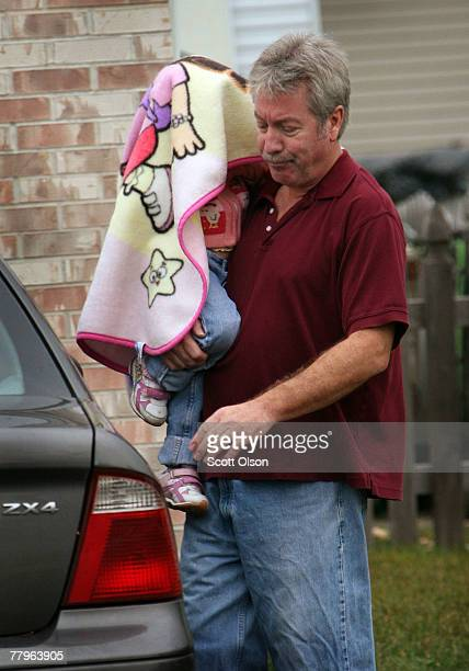 Former Bolingbrook Illinois police Sgt Drew Peterson carries his daughter to a car with her head covered by a blanket to shield her from the media in...