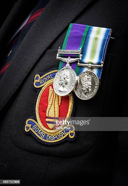 A former bomb disposal technician wears a blazer with the unit badge and medals outside St Paul's Cathedral following a service marking the 75th...