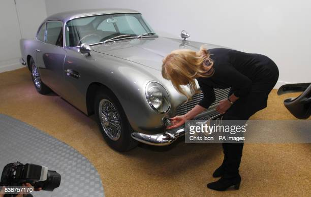 Former Bond girl Britt Ekland inspects the machine guns behind the indicator light of the original Aston Martin DB5 at a new exhibition Bond in...
