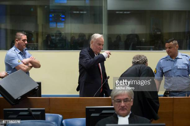 Former Bosnian military chief Ratko Mladic makes the sign of the cross over himself before appearing for the pronouncement of the Trial Judgement for...