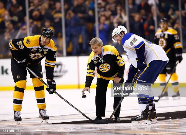 Former Boston Bruins player Bobby Orr drops the puck in front of Zdeno Chara of the Boston Bruins and David Backes of the St Louis Blues prior to the...