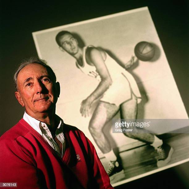 Former Boston Celtics Bob Cousy poses for a portrait with a black and white photo of himself in the background circa 1997 in Boston Massachusetts...