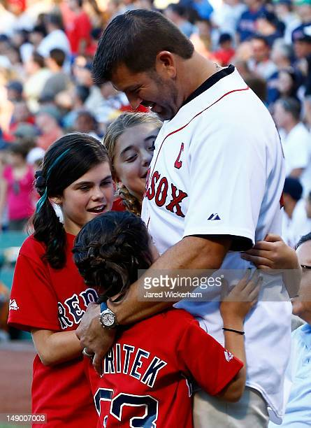 Former Boston Red Sox catcher and twotime World Series Champion Jason Varitek is hugged by his daughters while being honored on 'Thanks Tek Day' at...