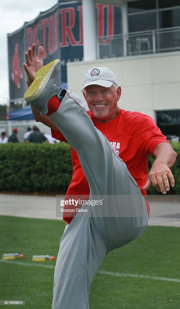 Former Boston Red Sox pitcher Bill Lee, 71, delights in showing some members of the team training staff how high he could still kick up his leg as they chat after practice on the day of the first full squad spring training workout at the Player Development Complex at Jet Blue Park in Fort Myers, FL on Feb. 19, 2018.