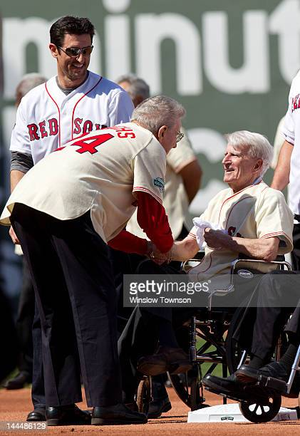 Former Boston Red Sox pitcher Paul Hinrichs shakes hands with Johnny Pesky as Hall of Famer Bobby Doerr looks on with back left to right Nomar...