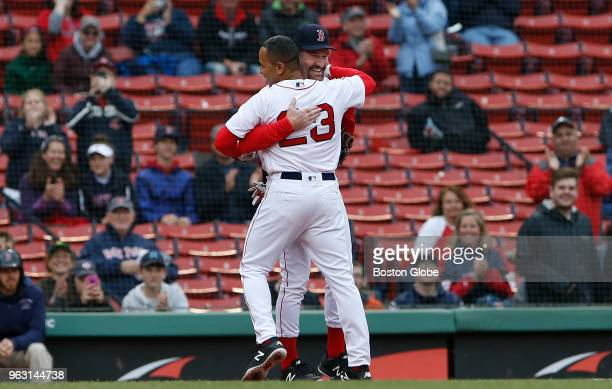 Former Boston Red Sox player Julio Lugo stops to hug Wade Boggs as he rounds the bases on a home run during the Red Sox alumni game at Fenway Park in...