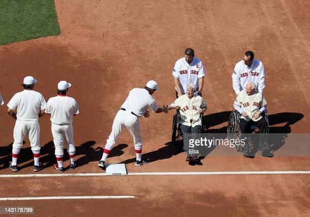 Former Boston Red Sox players Johnny Pesky and Bobby Doerr are wheeled off the field by Jason Varitek and Tim Wakefield before the game between the...