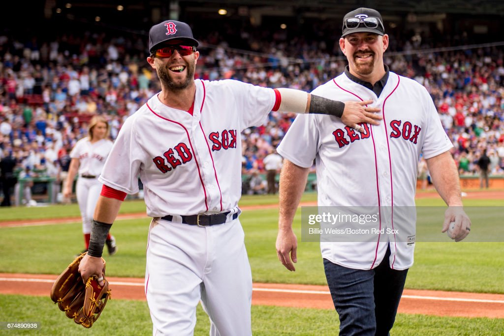 Former Boston Red Sox third baseman Kevin Youkilis (R) reacts with Dustin Pedroia #15 of the Boston Red Sox after throwing out the ceremonial first pitch before a game against the Chicago Cubs on April 29, 2017 at Fenway Park in Boston, Massachusetts.