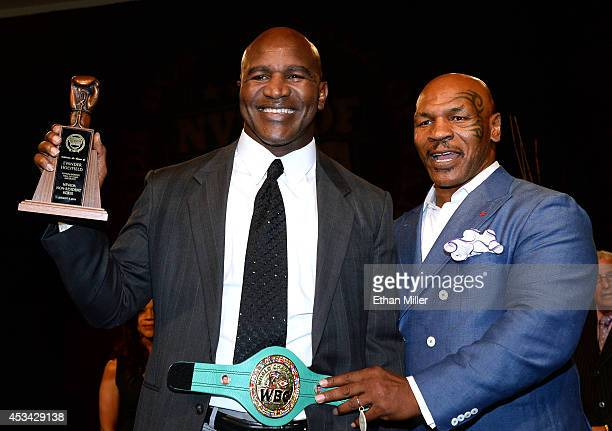 Former boxer Evander Holyfield is inducted into the Nevada Boxing Hall of Fame by former boxer Mike Tyson at the second annual induction gala at the...