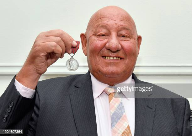 Former boxer Ronnie Russell poses for a photograph in London on March 2 with the George Medal awarded to him for defending the life of Britain's...