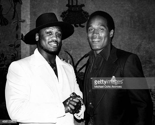 Former boxer 'Smokin' Joe Frazier shakes hands with former NFL player O J Simpson at PIPS private club on June 20 1979 in Beverly Hills California