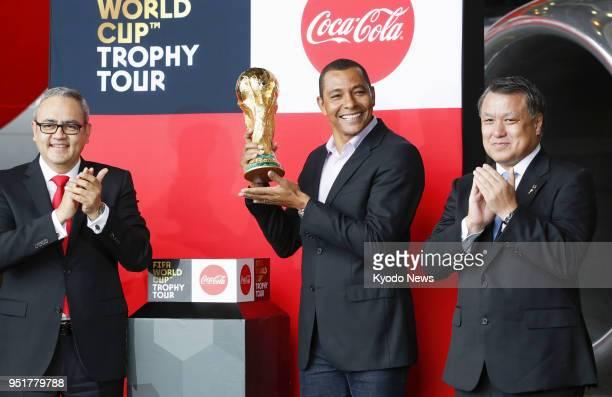 Former Brazil national football team defender Gilberto Silva alongside Japan Football Association President Kozo Tashima poses with the FIFA World...