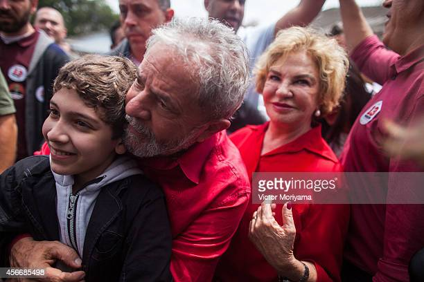 Former Brazil President Luiz Inacio Lula da Silva poses with supporters after voting during the first round of presidential elections on October 5,...