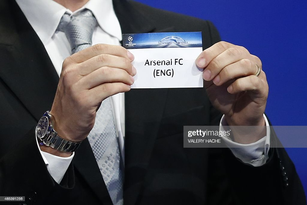 Former Brazilian football player Juliano Belletti shows the name of Arsenal football club during the UEFA Champions League Group stage draw ceremony, on August 27, 2015 in Monaco.