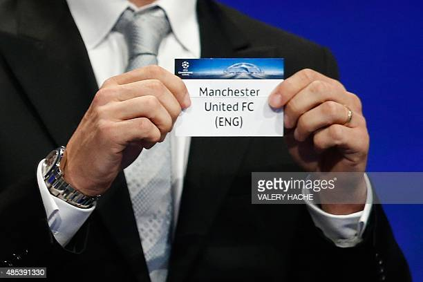 Former Brazilian football player Juliano Belletti shows the name of Manchester United football club during the UEFA Champions League Group stage draw...