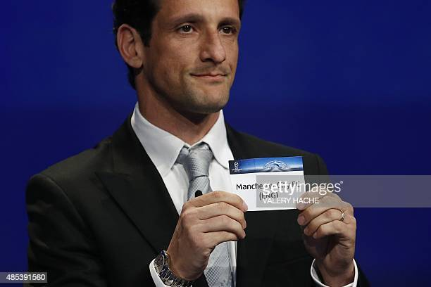 Former Brazilian football player Juliano Belletti shows the name of Manchester City football club during the UEFA Champions League Group stage draw...