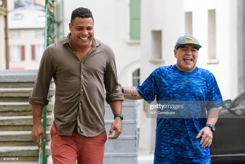 Former Brazilian football star Ronaldo (L) and former Argentinian football star Diego Maradona arrive to take part in 'The Gianni's game, the match of legends', a football match with football legends in honour of FIFA's President on July 7, 2017 in Brig. / AFP PHOTO / Fabrice COFFRINI