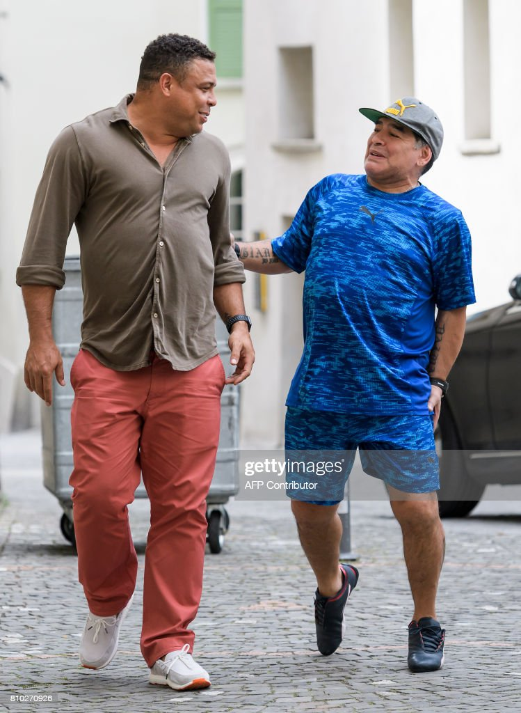 Former Brazilian football star Ronaldo (L) and former Argentinian football star Diego Maradona joke as they arrive to take part in 'The Gianni's game, the match of legends', a football match with football legends in honour of FIFA's President on July 7, 2017 in Brig. / AFP PHOTO / Fabrice COFFRINI