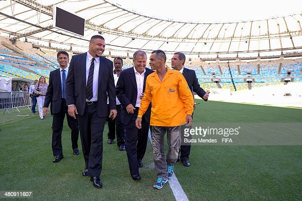 Former Brazilian football stars Zico and member of the Local Organizing Committee Ronaldo Nazario and Bebeto walk with workers during the 2014 FIFA...
