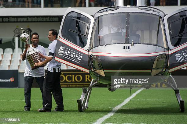 Former Brazilian footballer Edson Arantes do Nascimento aka 'Pele' ambassador of the 2014 World Cup lands on the pitch carrying the Copa Libertadores...
