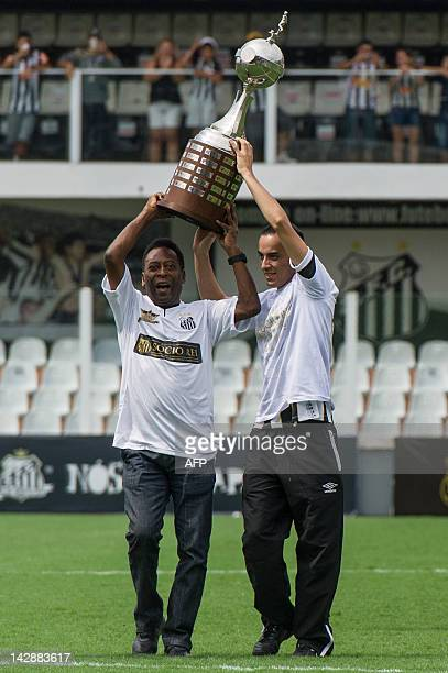 Former Brazilian footballer Edson Arantes do Nascimento aka 'Pele' ambassador of the 2014 World Cup carries the Copa Libertadores trophy during the...