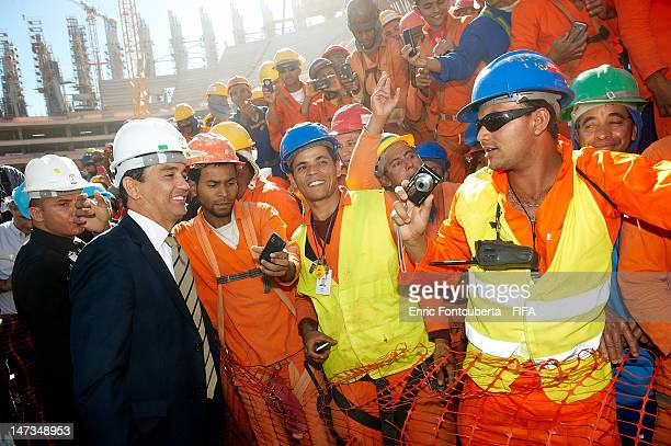 Former Brazilian national football player Bebeto poses with construction workers of National Stadium of Brasilia during the FIFA NorthEast Stadiums...