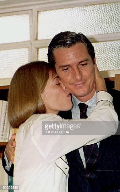 Former Brazilian President Fernando Collor de Mello gets a kiss 30 December 1992 from his wife Rosane at the end of a press conference where he...