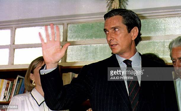 Former Brazilian President Fernando Collor de Mello waves to reporters 30 December 1992 after his press conference where he spoke about his...