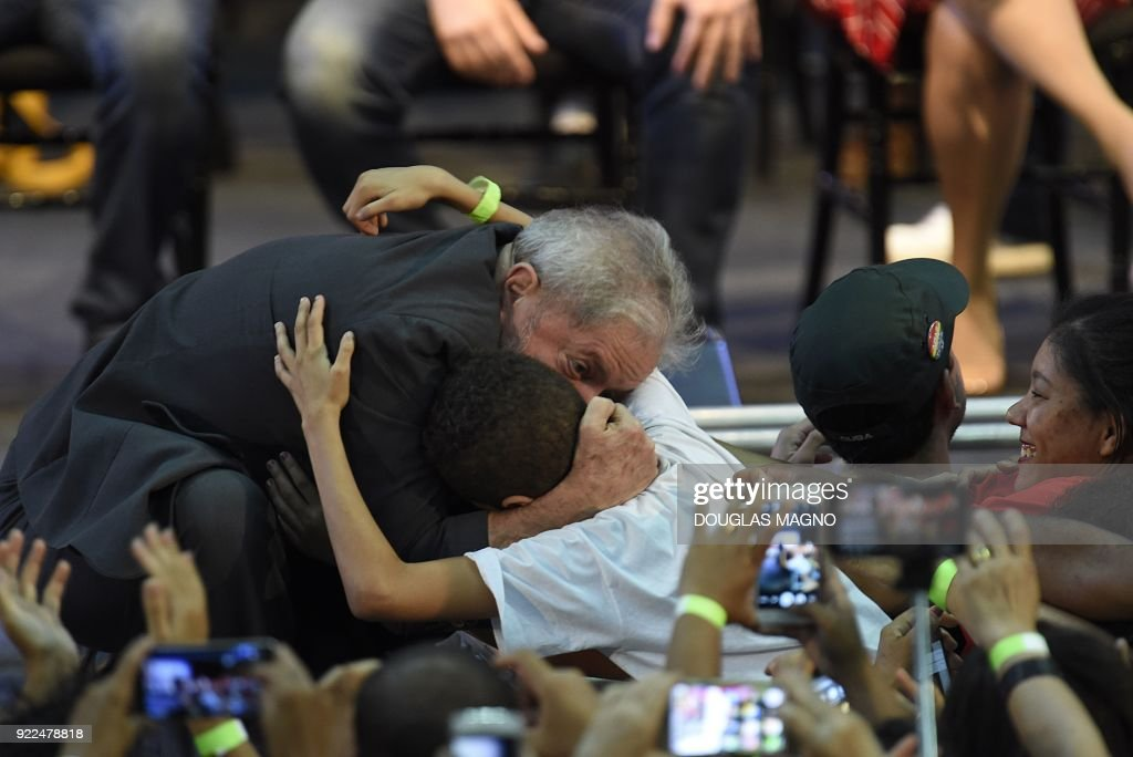 Former Brazilian president Luiz Inacio Lula da Silva hugs a boy during the launch of his pre-candidacy for the presidency, at the Expominas in Belo Horizonte, capital of Minas Gerais, Brazil, on Fe...
