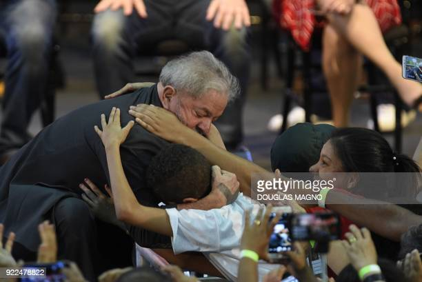 TOPSHOT Former Brazilian president Luiz Inacio Lula da Silva hugs a boy during the launch of his precandidacy for the presidency at the Expominas in...