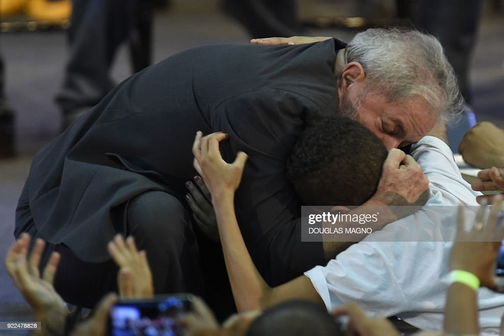 Former Brazilian president Luiz Inacio Lula da Silva hugs a boy during the launch of his pre-candidacy for the presidency, at the Expominas in Belo Horizonte, capital of Minas Gerais, Brazil, on February 21, 2018. The capital of Minas Gerais is the first to host an event of this kind since Lula's conviction for corruption was upheld by a federal appeals court. /