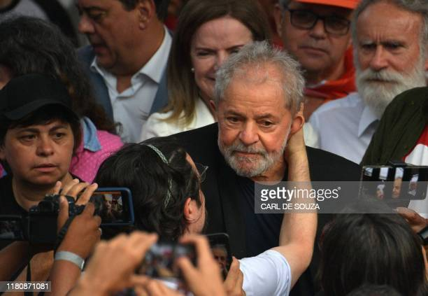 TOPSHOT Former Brazilian President Luiz Inacio Lula da Silva is greeted by supporters as he leaves the Federal Police Headquarters where he was...