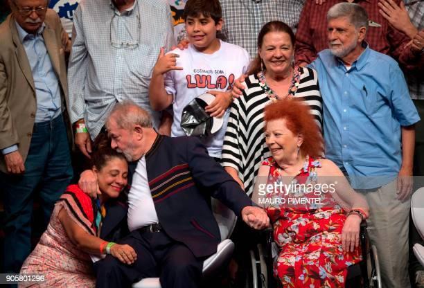 Former Brazilian president Luiz Inacio Lula da Silva kisses an actress next to Brazilian musician Beth Carvalho and former Foreign Minister Celso...
