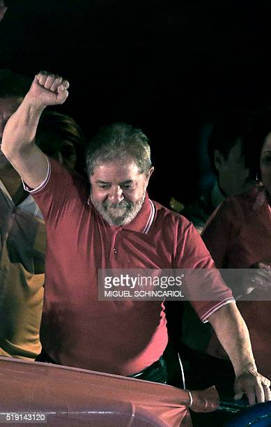 Former Brazilian President Luiz Inacio Lula da Silva raises his fist during a rally of unionists and members of the Workers Party in his support, in...
