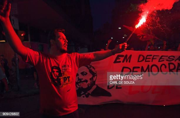 TOPSHOT A former Brazilian President Luiz Inacio Lula da Silva supporter lights a flare during a demonstration in the city centre of the state of Rio...